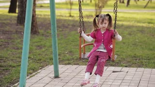 sad little girl swinging on a swing