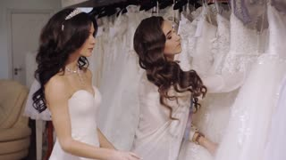 seller consultant helps the bride to choose a wedding dress in a trendy salon