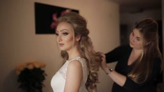 Sister helping bride button dress