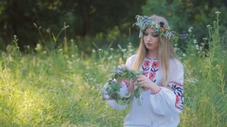 Slavic woman in an embroidered shirt patterns , weaves a wreath of wild flowers sitting by the fire .