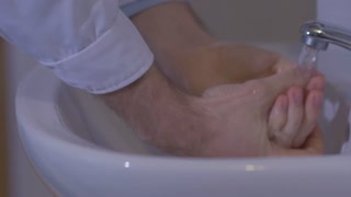 Slow motion doctor carefully wash their hands before surgery