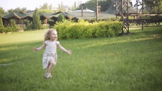 smiling curly-haired little girl runs across the grass to her mother