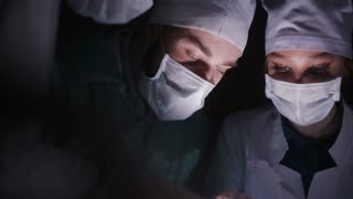 Surgeons team preforming operation in hospital operating theater, close up face. Surgeon operating patient,wearing surgical mask.