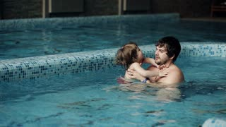 Swimming lessons. Father teaches son in the pool to swim