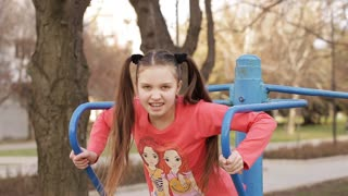 teen girl swings the press on the bar playground