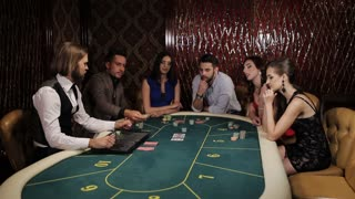 The company of players at the poker table place their bets.