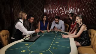 The company of players at the poker table. The dealer deals the players cards