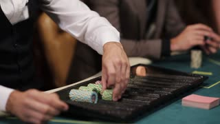 The dealer at the poker table lays chips under par