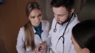 The doctor and two young intern looking at tablet and discuss the results of the patient survey