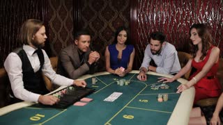 The game of poker. Girl in blue dress enjoys win at the casino.