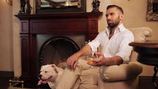 The man in the armchair by the fireplace drinking whiskey and petting his dog.