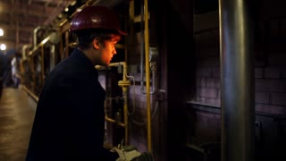 The man working at the shop monitors the temperature in the furnace. Male worker produces control the firing temperature in the furnace refractory bricks