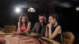 The rich man surrounded by two girls to play and win at the casino