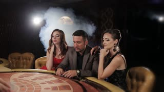 The rich man surrounded by two prostitutes play in a casino