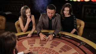 The rich man surrounded by two prostitutes to play and win at the casino