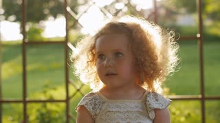 The setting sun plays in the curly hair. Portrait of the curly-haired girls.