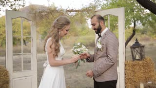 The wedding ceremony in the rustic style. The bride and groom dress each other wedding rings