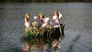 Three girls in the Slavic national costume in a boat floating on the river. girl posing in wreaths. Slavic girls in embroidered shirts. reflection on the water. bright sunshine