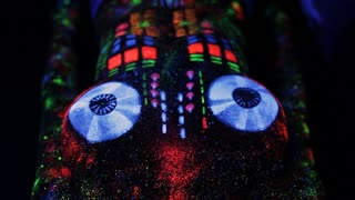 Topless girl painted in UV powder as a DJ panel.