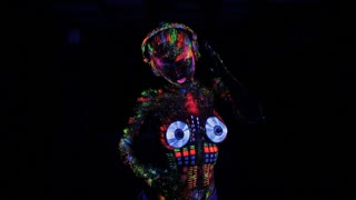 Topless woman painted UV powder as a DJ console dancing