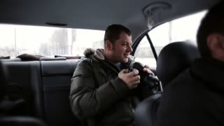 Tourist rides in a taxi and take pictures of the car winter landscapes