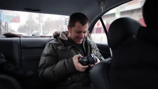 tourist rides in the winter interior taxis and viewing images on the camera. Tourist passenger still smiling looking at photos on your camera