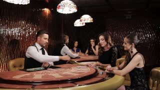 Two Beautiful Women Playing at the Table Blackjack in a Casino