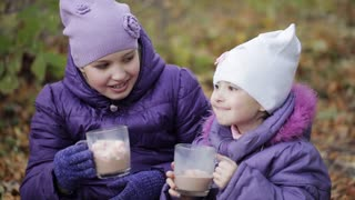 two sisters drink cocoa with marshmallows in the autumn park