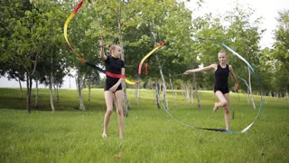 Two young gymnasts with tape performs exercises in the Park.