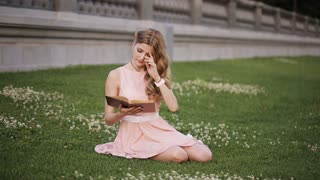 Very beautiful girl in the park on the grass with a book