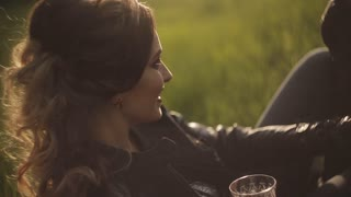 A beautiful couple in love in leather jackets on a picnic. red wine in glasses. Date at sunset in the soft rays of the sunlight