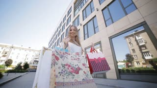 A beautiful girl with bright packages near the shopping center enjoys her shopping.