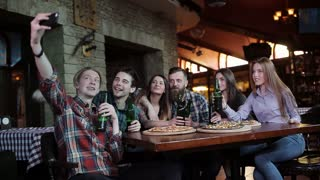 A company of friends resting in a pizzeria and making selfie on the background of pizza and beer. A young guy on his phone makes a selfie cheerful company in a pizzeria