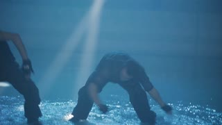 A group of guys are dancing active dance in water with splashes in the beam of a spotlight
