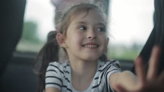 A little girl is riding in the bus sitting by the window