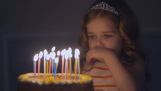 A little girl looks at candles on a festive cake and makes a wish in Slow motion