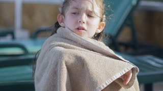a little girl, wrapped in a towel, with a dirty face, lonely sitting on sitting on a sun lounger by the pool, in the summer. She has a sad look. She wants to sleep