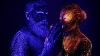 A man and a woman in the ultraviolet light caress each other. Fire and ice, two hypostases.