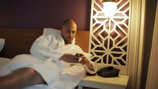 A man in a Bathrobe lying in bed and calls the reception of the hotel