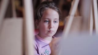A pretty little girl is painting a picture on canvas. studio of early development. art studio