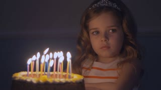 A sad little girl looks at a birthday cake and makes a wish that dad come home. Slow motion