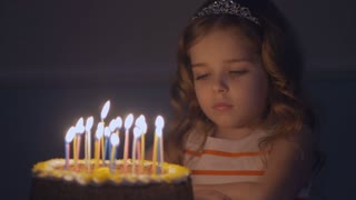 A sad little girl looks at a birthday cake and makes a wish that dad come home