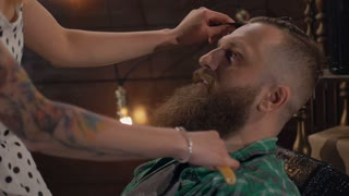 A sexual worker of a barber shop combs a brutal bearded man in Slow motion. The girl in a short dress sits on a brutal man and shaves him with a dangerous razor.