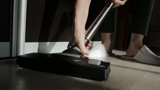 A woman changes the nozzle on the vacuum cleaner while cleaning the house.