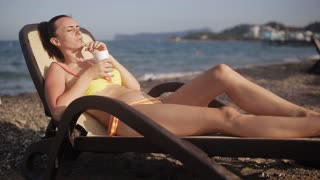 A woman lying on a sun lounger on the beach and drinking a cocktail