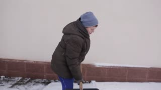 A woman pensioner with a shovel-cleans snow-covered path near the house