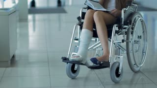 A young girl in a wheelchair is reading a book. Patient in a wheelchair in the hospital corridor.