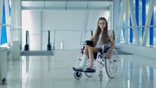 A young girl in a wheelchair is standing in the corridor of the hospital.