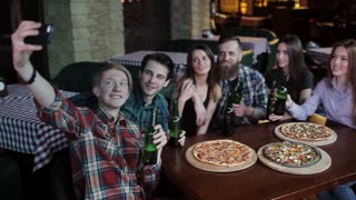 A young guy on his phone makes a selfie cheerful company in a pizzeria