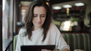 a young woman in a cafe makes purchases on the Internet using a tablet and wifi